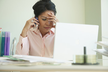 Frustrated Asian businesswoman talking on cell phone at desk