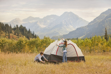 Caucasian couple setting up tent