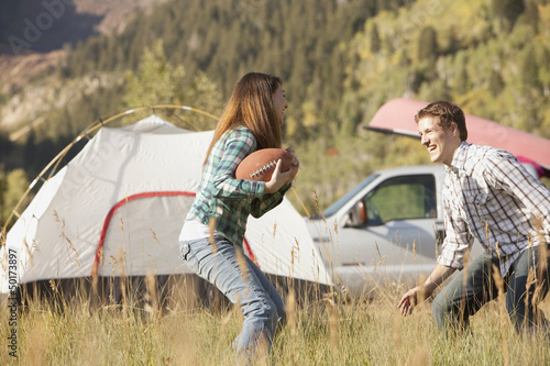 Caucasian couple playing football at campsite