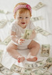 Caucasian baby girl playing with twenty dollar bills