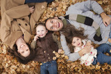 Caucasian family laying in autumn leaves