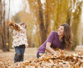 Caucasian girl throwing autumn leaves at mother