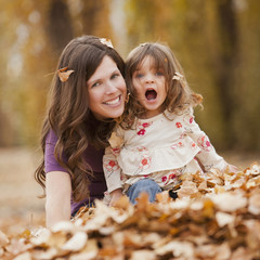 Caucasian mother and daughter playing in autumn leaves