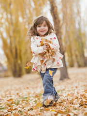 Caucasian girl playing with autumn leaves