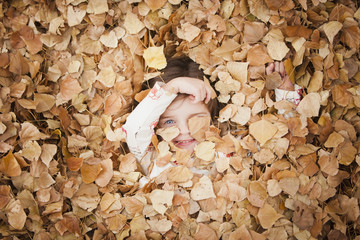 Caucasian girl laying in autumn leaves