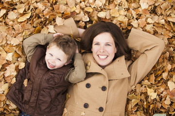 Caucasian mother and son laying autumn leaves