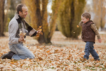 Caucasian father and son playing in autumn leaves