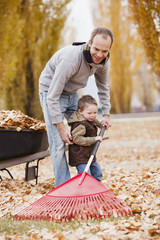 Caucasian father and son raking autumn leaves