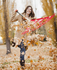 Caucasian woman raking autumn leaves