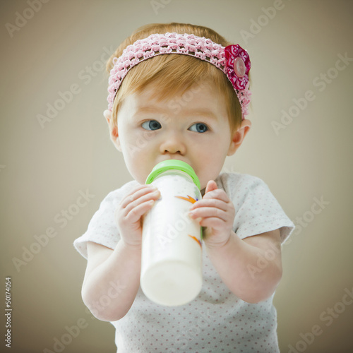 Caucasian baby girl drinking bottle
