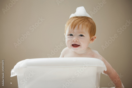 Caucasian baby girl having a bath
