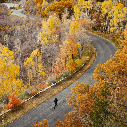 Caucasian woman running along autumn road