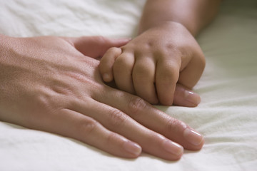 Hispanic mother and baby boy holding hands