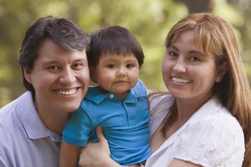 Smiling Hispanic parents holding baby boy