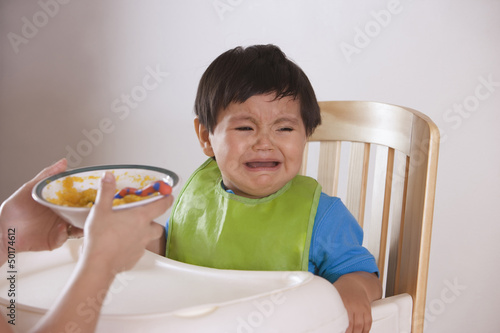 Hispanic mother trying to feed crying baby boy