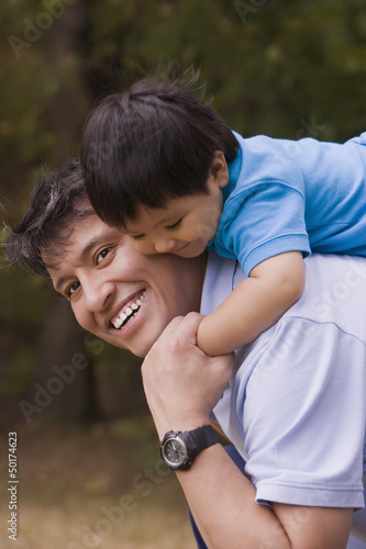 Smiling father giving piggyback to baby boy