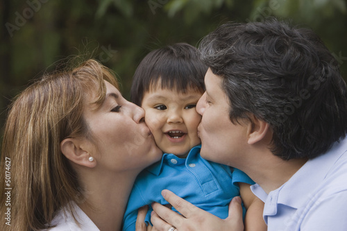 Hispanic parents kissing baby boy