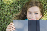 Smiling girl laying on ground reading book