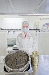 Hispanic worker filling tins with caviar