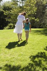 Mother and daughter walking together in grass