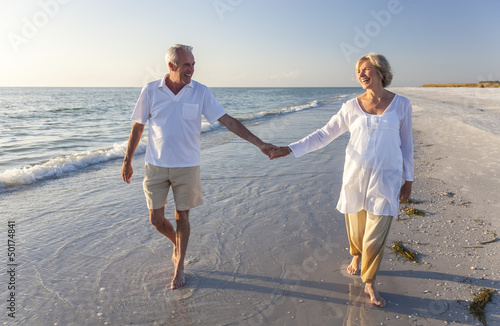 Leinwanddruck Bild Happy Senior Couple Walking Holding Hands Tropical Beach