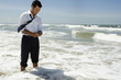 Businessman text messaging on cell phone while standing in ocean