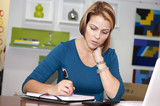 Hispanic businesswoman writing in notebook