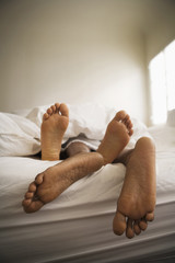 Barefeet of couple laying in bed together