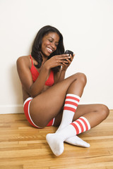 Woman in underwear text messaging on cell phone