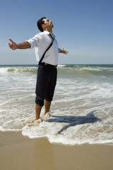 Businessman wading in ocean