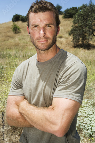 Serious man standing in remote field