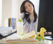 Japanese woman on phone with baby toys on desk