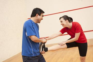 Hispanic couple stretching before racquetball