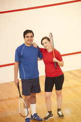 Hispanic couple playing racquetball