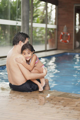 Hispanic father and daughter sitting on edge of swimming pool