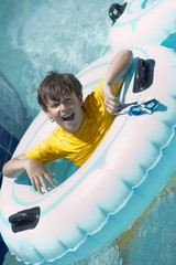 Hispanic boy floating on raft in swimming pool