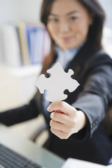 Japanese businesswoman holding puzzle piece