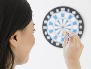 Japanese woman throwing dart at dartboard