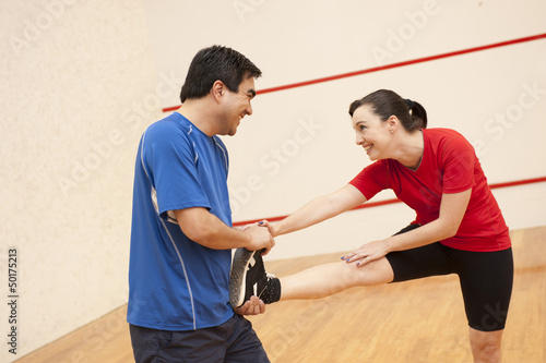 Hispanic couple stretching before racquetball