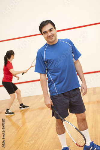 Hispanic couple playing racquetball