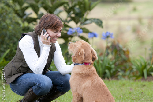 Smiling Hispanic woman talking on cell phone and petting dog