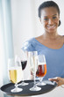 Black waitress carrying tray of drinks