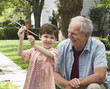 Caucasian boy and grandfather playing with toy airplane