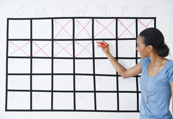 Black woman marking the days off calendar