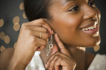 Black woman putting on earring