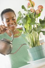 Black woman watering plant