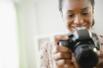 Black woman using digital SLR camera