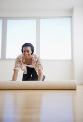 Black woman unrolling carpet in new home