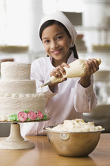 Hispanic girl icing wedding cake