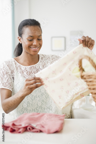 Black woman folding laundry